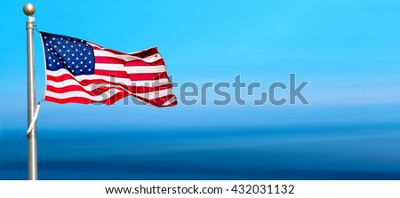 United States flag blows in the wind against a blue sky panoramic view - stock photo