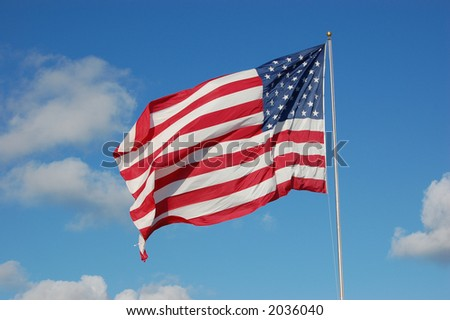 United States Flag waving in a blue sky - stock photo