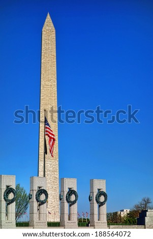 United States National World War II Memorial dedicated to Americans service in the armed forces with state named pillars and Washington Monument on the Mall over bright blue sky in US capital of DC