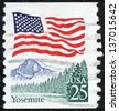 UNITED STATES OF AMERICA - CIRCA 1988: a stamp printed in the USA shows USA Flag over Yosemite Valley, circa 1988 - stock photo