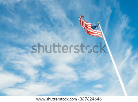 United States of America flag with cloudy blue sky - stock photo