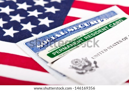 United States of America social security and green card with US flag on the background. Immigration concept. Closeup with shallow depth of field. - stock photo
