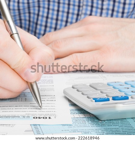 United States of America Tax Form 1040 - male filling out tax form - 1 to 1 ratio - stock photo