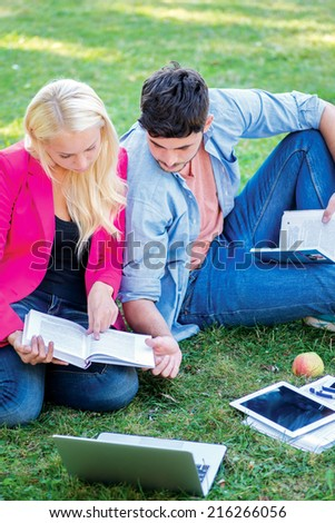 University days. Pair of beautiful student sitting on the grass reading a book while teaching lessons on a break near the building of the university. - stock photo