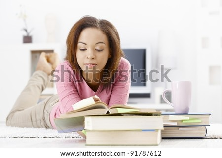 University girl studying at home, reading book, lying on floor.? - stock photo