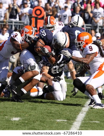 UNIVERSITY PARK, PA - OCT 9: Penn State's Evan Royster #22 is tackled by a host of Illinois players  during a loss at Beaver Stadium October 9, 2010 in University Park, PA - stock photo