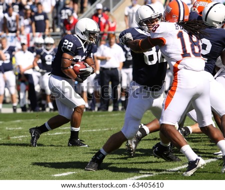 UNIVERSITY PARK, PA - OCT 9: Penn State's running back #22 Evan Royster is tackled during a game against Illinois at Beaver Stadium October 9, 2010 in University Park, PA - stock photo