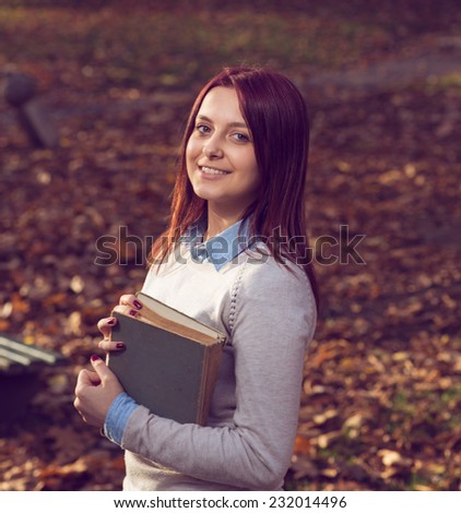 University redhead girl staning in park and reading a book