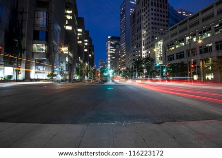University Street in Montreal with silhouette cars with red rear light and traffic light, early in the morning with office building in background to dusk. - stock photo