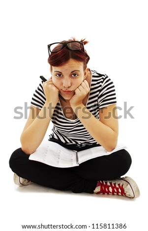 University student bored, frustrated and overwhelmed by studying homework. Young woman sitting down on floor isolated on white background. - stock photo