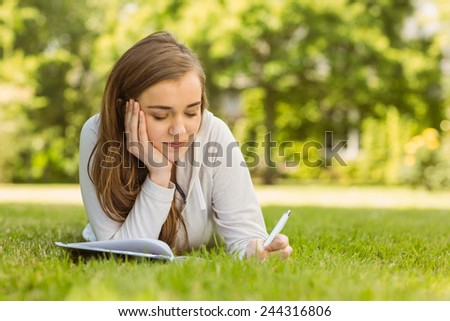 University student lying and writing on notepad in park at school - stock photo