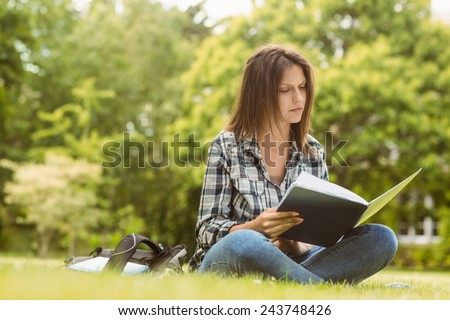 University student standing reading book in park at school - stock photo