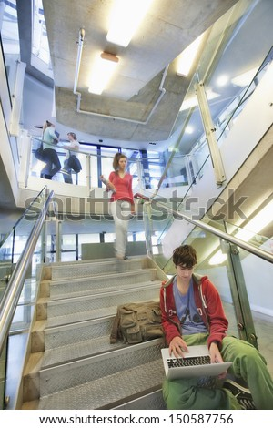 University student using laptop on staircase with friends behind - stock photo