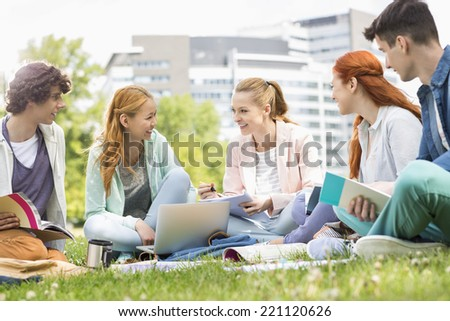 University students studying together on grass - stock photo