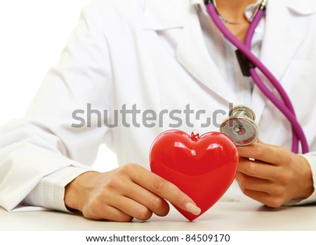 Unknown female doctor examining red heart