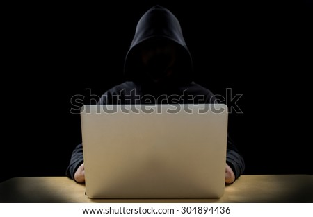 unknown hacker working on laptop