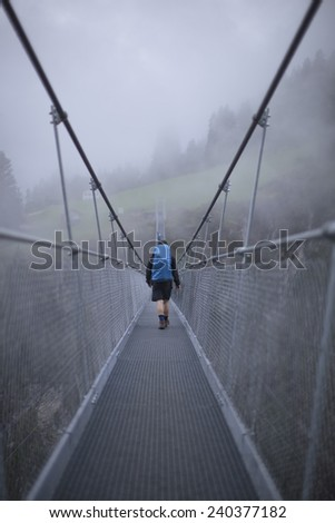 Unknown hiker crossing a metal bridge across a foggy canyon in the Austrian Alps with a large backpack - stock photo