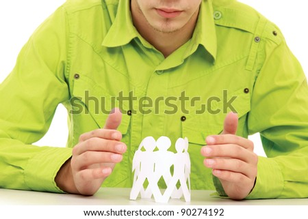 Unknown man taking care about paper people while sitting at desk isolated on white background - stock photo