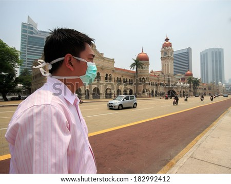 Unknown man wearing a face mask because of thick haze. - stock photo