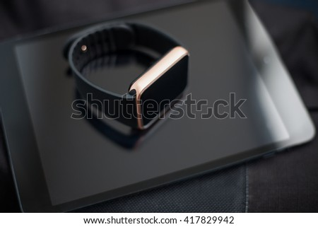 Unknown smart wrist watch laying on a tablet pc. This gadgets will let you always stay connected to the social media and internet technologies. Work and have fun from anywhere you want.
