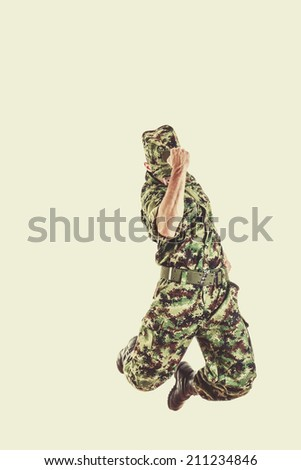 unknown soldier with hidden face in green camouflage uniform jumping up in air with fist sign of success - stock photo
