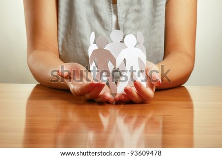 Unknown woman holding paper people sitting at the desk, isolated on grey - stock photo
