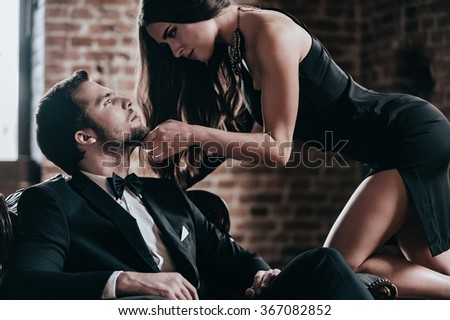 Unleashed desire. Beautiful young woman in cocktail dress leaning to her boyfriend sitting in chair while looking at each other in loft interior - stock photo
