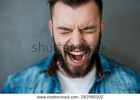 Unleashed emotions. Frustrated young man keeping eyes closed and mouth opened while standing against grey background - stock photo