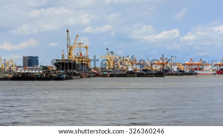Unloading containers from cargo ships at Bangkok Port, Thailand - stock photo