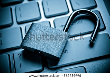 unlock security lock on computer keyboard - computer security breach concept - stock photo