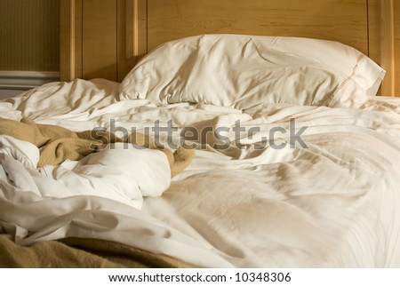 unmade bed in hotel room - stock photo