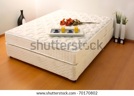 Unmade bed with breakfast tray - stock photo
