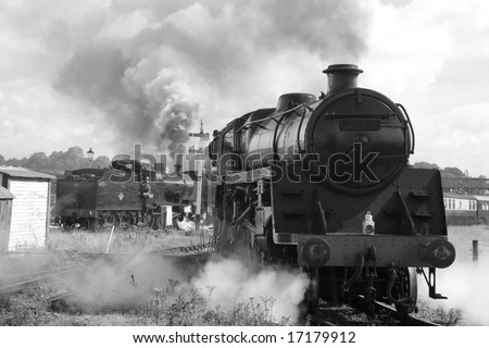 UNMARKED VINTAGE STEAM TRAINS IN STATION PHOTOGRAPHED IN BLACK AND WHITE - stock photo