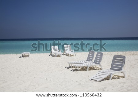 Unoccupied beach chairs on the sand next to the ocean. - stock photo