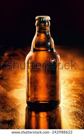 Unopened brown glass bottle of chilled beer backlit on a wooden bar counter , unlabeled for your advertising - stock photo