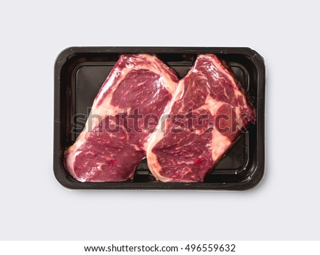 Unopened vacuum pack of 2 raw sirloin beef steaks isolated on white background, without label
