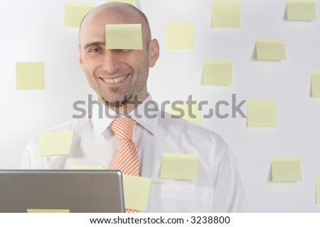 Unorganized businessman uses post-it notes to keep from forgetting important details and appointments. - stock photo