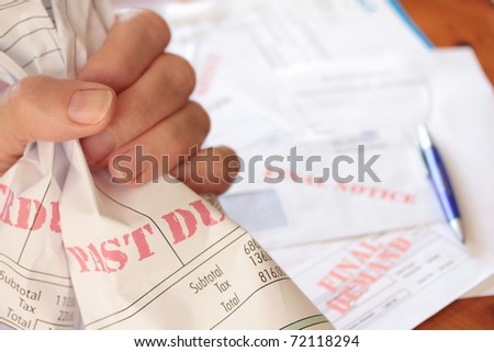 Unpaid Bills Clutched in Hand - stock photo
