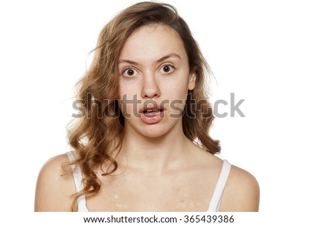 unpleasantly surprised young woman without make-up - stock photo