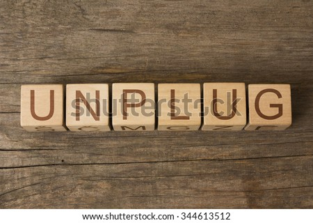 UNPLUG text on a wooden background