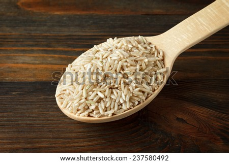 Unpolished rice in a wooden spoon on wood