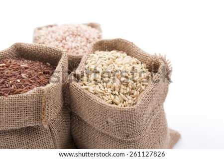 unpolished rice (whole grain) in a burlap bag on a white background - stock photo