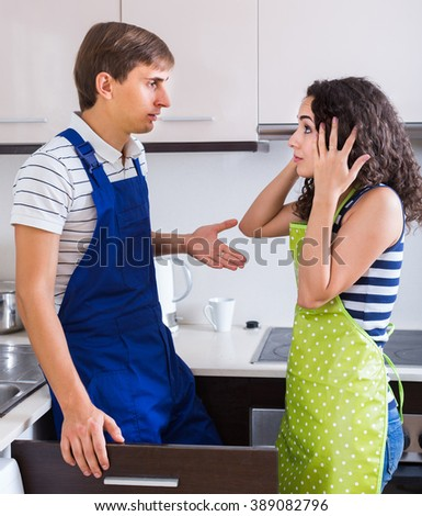 Unprofessional adult american plumber asking furious young woman for bribes indoors - stock photo