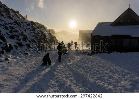Unrecognisable people protect themselves and play backlit by fading sun in snow storm - stock photo