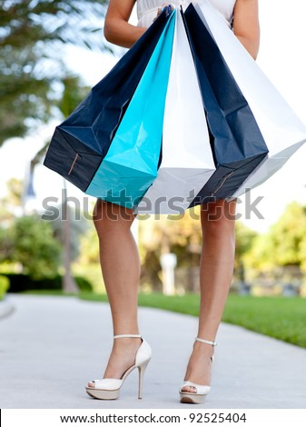 Unrecognizable attractive woman holding shopping bags - outdoors - stock photo
