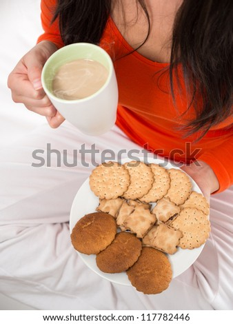 Unrecognizable brunette woman holding breakfast . Cup of hot steaming coffee and plate of biscuits. - stock photo