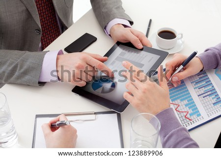 Unrecognizable business colleagues working together and using a digital tablet - stock photo