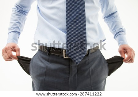 Unrecognizable businessman  demonstrating his empty pockets, white background - stock photo