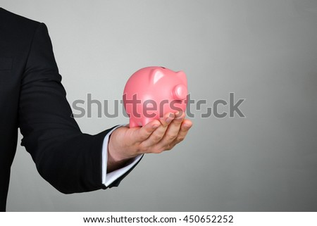 Unrecognizable businessman holding pink piggy bank - stock photo