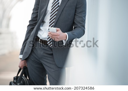 Unrecognizable businessman in suit using smartphone in office - stock photo